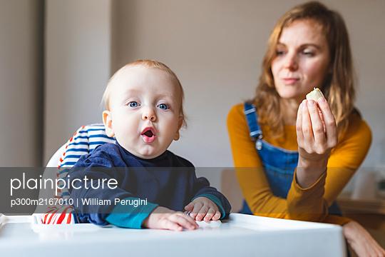 Portrait of baby boy with his mother siting in highchair - p300m2167010 von William Perugini