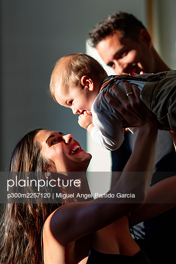 Smiling woman playing with baby boy while standing by man at home - p300m2257120 by Miguel Angel Partido Garcia