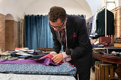Mature man choosing fabrics in studio - p1166m2261420 by Cavan Images