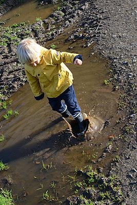 Toddler splashing in puddle - p1631m2228670 by Raphaël Lorand