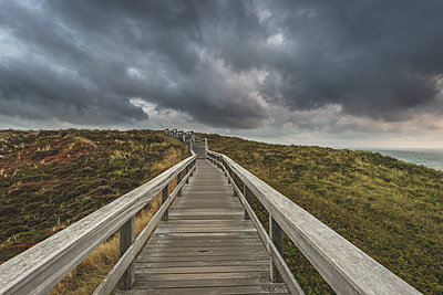 Germany, Schleswig-Holstein, Sylt, Wenningstedt, boardwalk to the beach under rain clouds - p300m2042208 by Kerstin Bittner