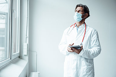 Male doctor wearing protective face mask holding digital tablet while standing by window in clinic - p300m2293754 by Joseffson