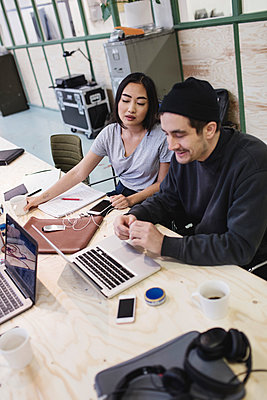 Young woman and man using laptop at desk in office - p426m1407182 by Maskot