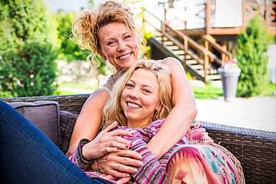 Mother and daughter hugging on backyard sofa - p555m1409726 by Shestock