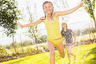 Caucasian girls playing in sprinkler in backyard - p555m1415624 by Mike Kemp