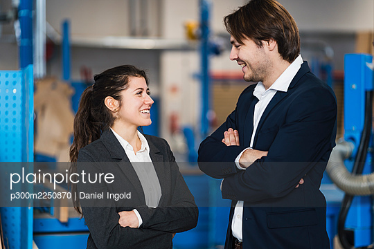 Young business people smiling while standing at industry - p300m2250870 by Daniel Ingold
