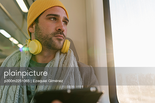 Man with digital tablet looking away while sitting in train - p300m2251065 by Ezequiel Giménez