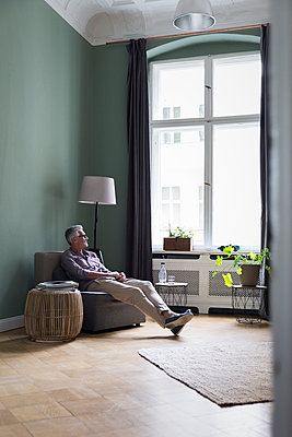 Relaxed mature man sitting at home - p300m2030161 by Rainer Berg