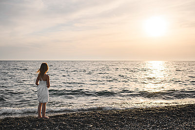 Little girl in white dress looking at sunset over the sea - p300m2103318 by Ekaterina Yakunina