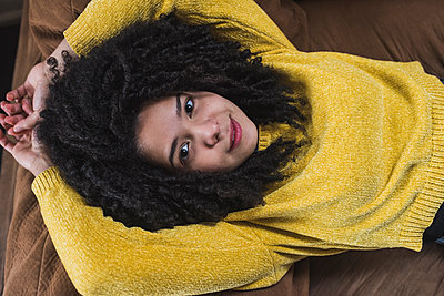 Curly haired woman lying on sofa at home - p300m2264972 by MORNINGVIEW AGENCY