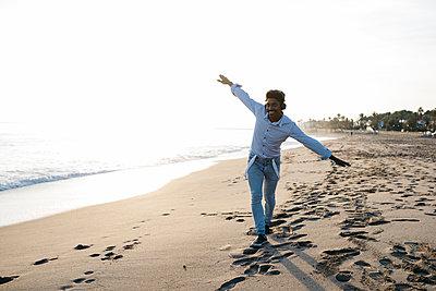 Playful man imitating airplane while while walking at beach - p300m2267012 by Josep Rovirosa