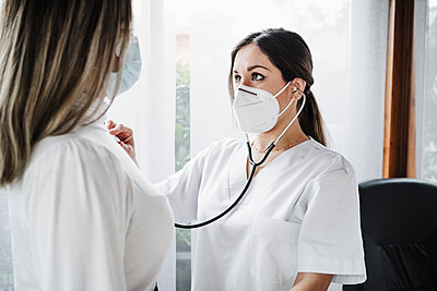 Female doctor wearing protective face mask checking patient at clinic - p300m2274843 by Eva Blanco