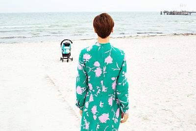 Frau schaut auf leeren Kinderwagen - p432m1487275 von mia takahara
