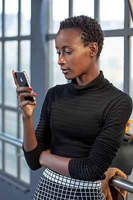 Junge Frau wartet und blickt auf Smartphone - p770m2065568 von mbphoto