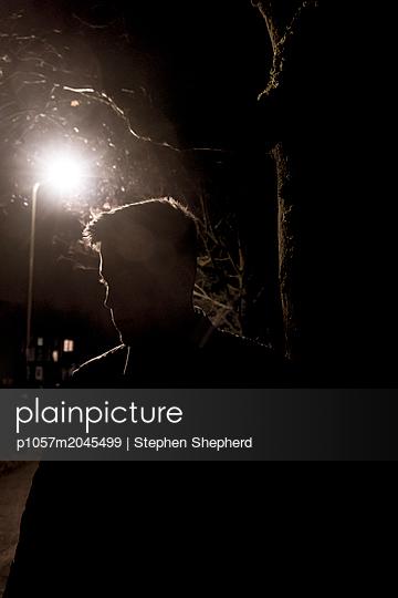 Silhouette eines junges Mannes in der Dunkelheit - p1057m2045499 von Stephen Shepherd