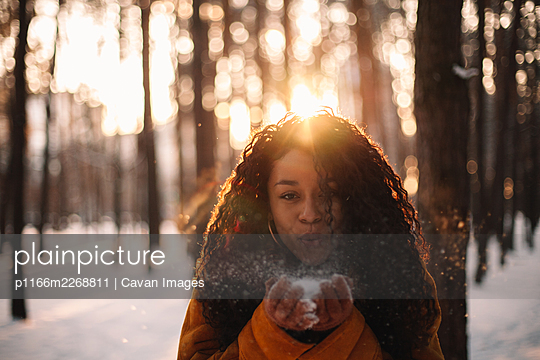 Woman blowing snow standing in park at sunset during winter - p1166m2268811 by Cavan Images