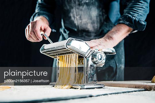 Hobby chef making fresh tagliatelle with pasta machine - p300m2156357 by Joseffson