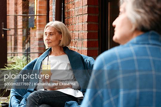 Mature female friends sitting at sidewalk cafe - p300m2277697 by Katharina und Ekaterina