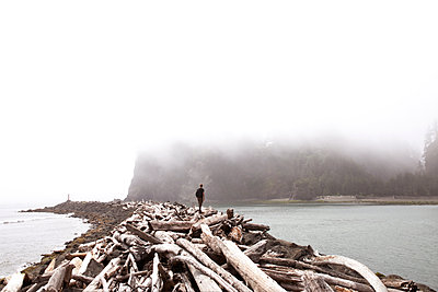 Teenager standing on driftwoods amidst sea during foggy weather - p1166m1087939f by Bethany Beeson