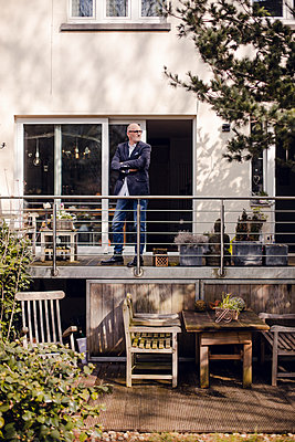 Senior man standing on his veranda, looking proud - p300m1588104 von Gustafsson