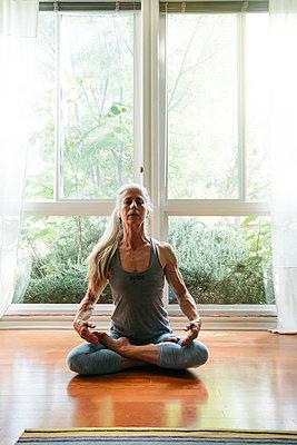 Caucasian woman meditating on floor - p555m1305084 by Inti St Clair