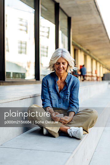 Mature businesswoman sitting cross-legged on steps in the city, using smartphone - p300m2156684 by Sofie Delauw