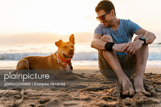 Smiling man looking at his dog while relaxing at beach - p300m2206665 by Ezequiel Giménez