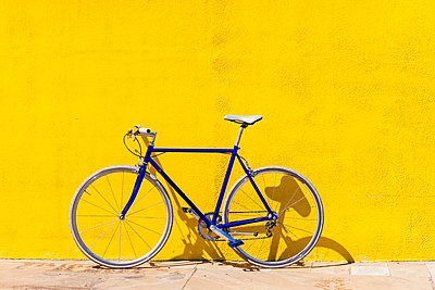 Bicycle parked on sidewalk by yellow wall during sunny day - p1166m2060567 by Cavan Social