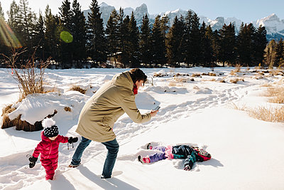 Family playing in snow, making snow angel - p1192m2088122 by Hero Images