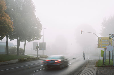 Man and dog crossing street on misty day in autumn - p300m2041849 by Frank Röder