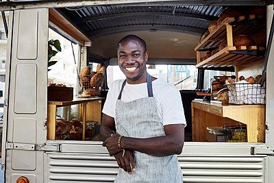 Portrait of smiling mid adult male owner standing outside food truck - p426m1536950 by Maskot