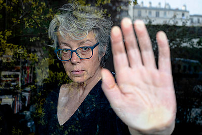 Grey-haired woman behind window - p445m2173645 by Marie Docher