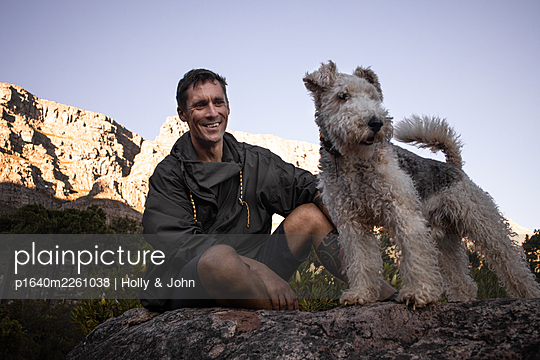 Hiker and his dog on a rock - p1640m2261038 by Holly & John