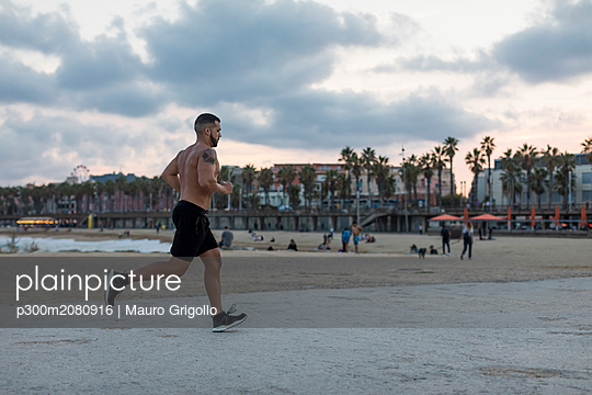 Barechested muscular man running on waterfront promenade - p300m2080916 by Mauro Grigollo