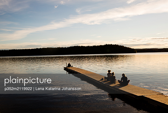 Young woman on the pier of a lake in Dalarna Sweden - p352m2119922 by Lena Katarina Johansson