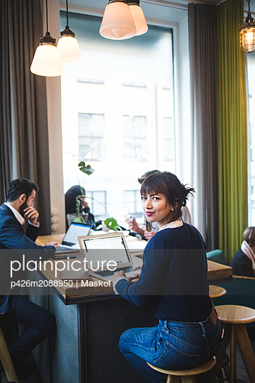 Portrait of smiling female professional sitting with laptop at table in office - p426m2088950 by Maskot