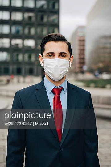 Portrait of businessman in office park during pandemic - p426m2270347 by Maskot