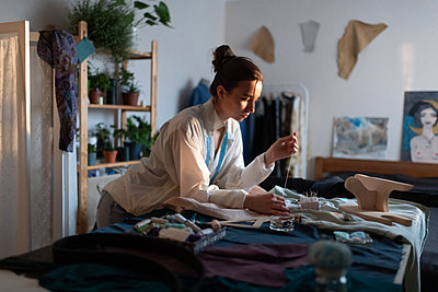 Focused woman sewing clothes in modern home office - p1166m2218579 by Cavan Images