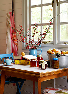 Twig arrangement and jam with apples on kitchen table at window in Isle of Wight home;  UK - p349m920049 by Rachel Whiting