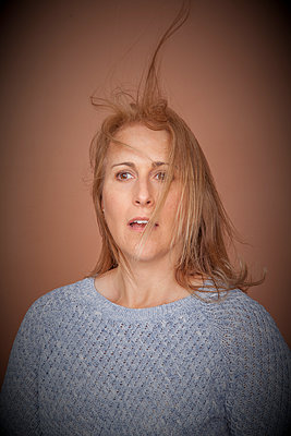 Woman with hair blowing - p397m1066066 by Peter Glass