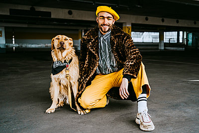 Full length of smiling young man with golden retriever in parking garage - p426m2279702 by Maskot