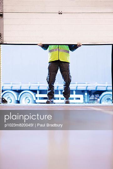 Worker lifting door in warehouse - p1023m820045f by Paul Bradbury