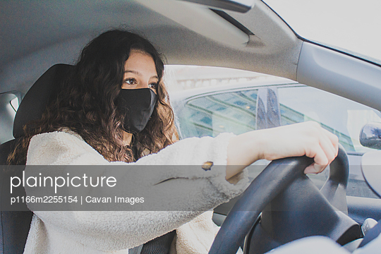 young woman driving with protective mask - p1166m2255154 by Cavan Images