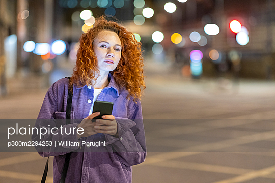 Redhead woman with mobile phone looking away while standing on crossroad at night - p300m2294253 by William Perugini