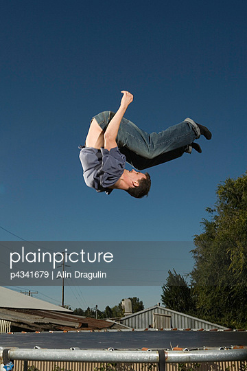 Young man jumping in mid-air, low angle view - p4341679 by Alin Dragulin
