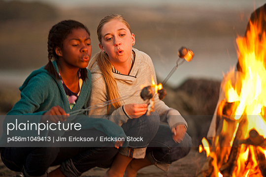 Teenage girls roasting marshmallows over a campfire - p456m1049413 by Jim Erickson / Erickson Stock