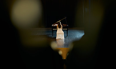a girl dressed in white with her back to the audience plays a black grand piano on a stage. - p1166m2152151 by Cavan Images