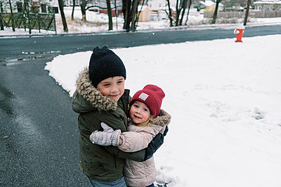Siblings hugging each other in their driveway while playing in snow. - p1166m2189732 by Cavan Images