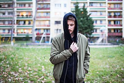 Junger Mann mit Kapuzenpulli vor Plattenbau - p1301m1132715 von Delia Baum