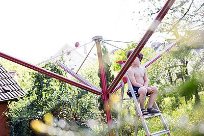 Kind sitzt auf Leiter im Garten - p1308m1136822 von felice douglas